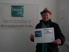 """A smiling person with a blue scarf holding a sign which reads""""Proud2Be different"""""""