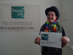 """A smiling person wearing rainbow flowers holding a sign which reads """"Proud2Be lesbian"""""""