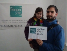 """A person holding a young child holding  as sign which reads """"Proud2Be a supporter of LGBT people"""""""