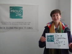 """A person with short brown hair holding a handwritten sign which reads """"I'm a supporter of LGBT!"""" with a heart shape drawn at the bottom"""