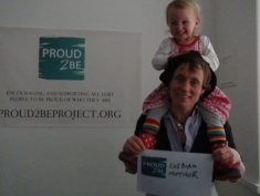 """A photograph of a smiling person holding a sign which reads""""Proud2Be a lesbian Mother"""". They have a smiling young child sitting on their shoulders wearing a pink dress, rainbow socks and spotty wellies."""