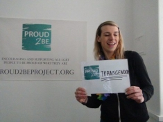 """A smiling person holding a sign which reads""""Proud2Be transgender"""""""
