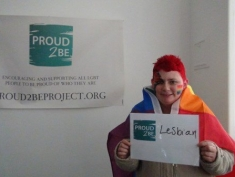 """A person wearing a rainbow flag as a cape and with another rainbow flag painted on their cheek holding a sign which reads """"Proud2Be lesbian"""""""