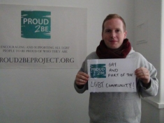 """A photograph of Proud2Be co-founder Max holding a sign which reads""""Proud2Be gay & part of the LGBT community"""".  Behind them is a poster for which reads """"Proud2Be. Encouraging and supporting all LGBT people to be proud of who they are. Proud2BeProject.org"""