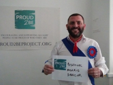 """A person wearing a blue sash, red necktie and red and blue rosette holding a sign which reads """"Proud2Be a bisexual morris dancer"""""""