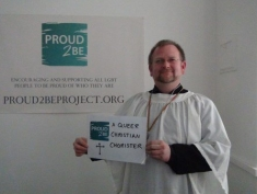"""A person in choir dress holding a sign which reads""""Proud2Be a queer christian chorister"""""""