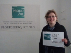 """A smiling person holding a sign which reads """"Proud2Be LGBT & disabled"""""""
