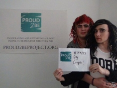 """Two people in drag holding a sign which reads""""Proud2Be a happy gay couple"""""""