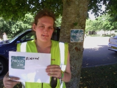 """Photograph of a person with long hair and  a high-vis jacket holding a sign """"Proud2Be Bisexual"""""""