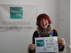 """A person with a rainbow painted on their face holding a sign which reads """"Proud2Be a bi single Mum"""""""