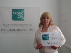 """A person with blonde hair holding a sign  reading 'Proud2Be Trans Woman"""""""