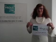 """A person holding a sign reading""""Proud2Be transgender woman"""""""