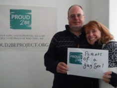 """A couple hugging and holding a sign which reads """"Proud2Be Parents of a gay Son"""""""