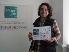 """A person with a flannel shirt holding a sign which reads """"Proud2Be gay! (But with some straight tendencies)"""""""