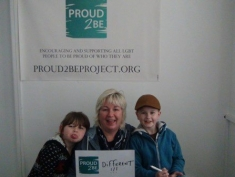 """A person crouched down next to two children holding a sign which reads """"Proud2Be different!!!"""" One of the children is sticking their tongue out at the camera"""