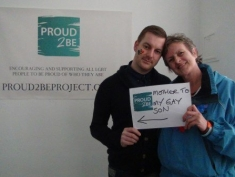 """A person holding a sign with """"Proud2Be Mother to my gay Son"""" written above an arrow which points to the person standing next to them, with their heads touching"""