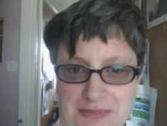 """Photograph of a  person wearing glasses with text saying """"Cuthbert is Proud2Be trans+'"""