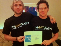 Photograph of two people in matching 'thegayuk.com' t-shirts. They are standing holding a sign with Graham and Jake are Poud2Be gay written on it.