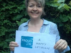"""Photograph of Sarah, wearing a blue shirt, smiling and holding a sign which reads  """"Proud2Be a happy lesbian!"""" and has a heart shape drawn on it"""