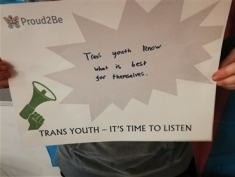 "A young trans person holding a sign with ""Trans Youth - it's time to listen"" printed at the bottom. They are holding it over their face  on it have  written in black marker  ""Trans youth know what is best for themselves"""