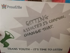 "A young trans person holding a sign with ""Trans Youth - it's time to listen"" printed at the bottom. They are holding it over their face  on it have  written in black marker  ""Getting assulted is common. Change that"""