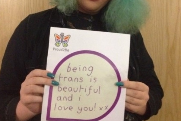 """A person holding a hand-written sign reading """"being trans is beautiful and I love you! xx"""""""