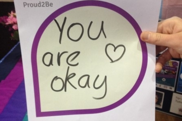 """A person holding a hand-written sign reading """"you are okay"""" followed by a heart"""