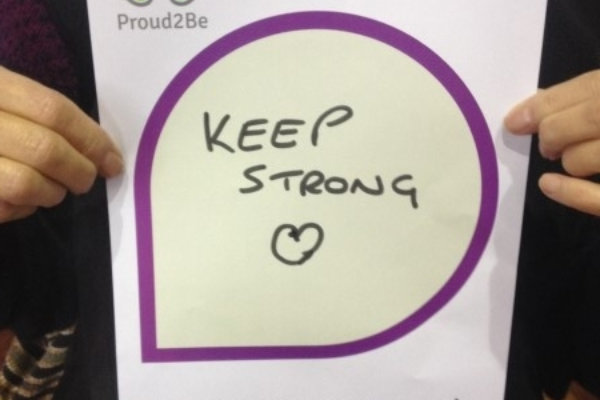 """A person holding a hand-written sign reading """"keep strong"""" with a heart drawn on"""