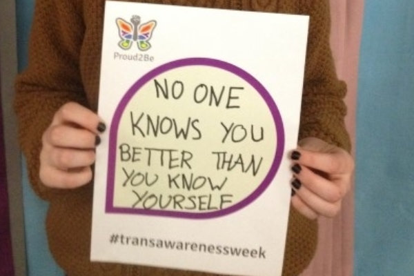 """A person holding a hand-written sign reading """"No one knows you better than you know yourself"""""""