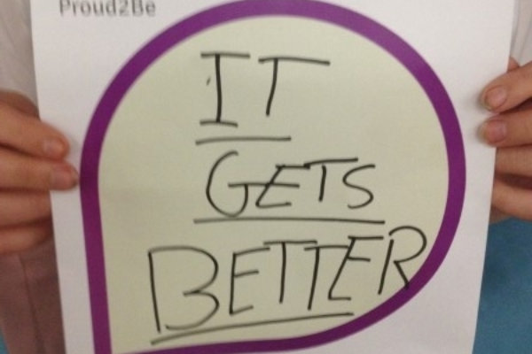 """A person holding a hand-written sign reading """"It gets Better"""""""