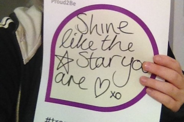 """A person holding a hand-written sign reading """"Shine like the star you are xo"""" There is a star and a heart drawn on the sign"""