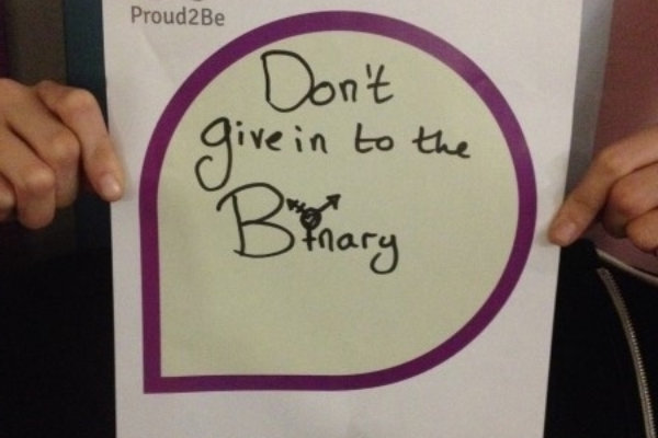 """A person holding a hand-written sign reading """"don't give in to the Binary"""" The 'i' in binary is the trans symbol"""