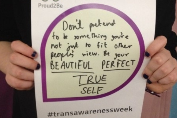 """A person holding a hand-written sign reading """"Don't pretend to be something you're not just to fit other people's view. Be your Beautiful Perfect True Self"""""""