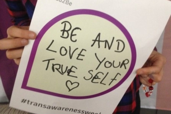 """A person holding a hand-written sign reading """"Be and love your true self"""" followed by a heart"""